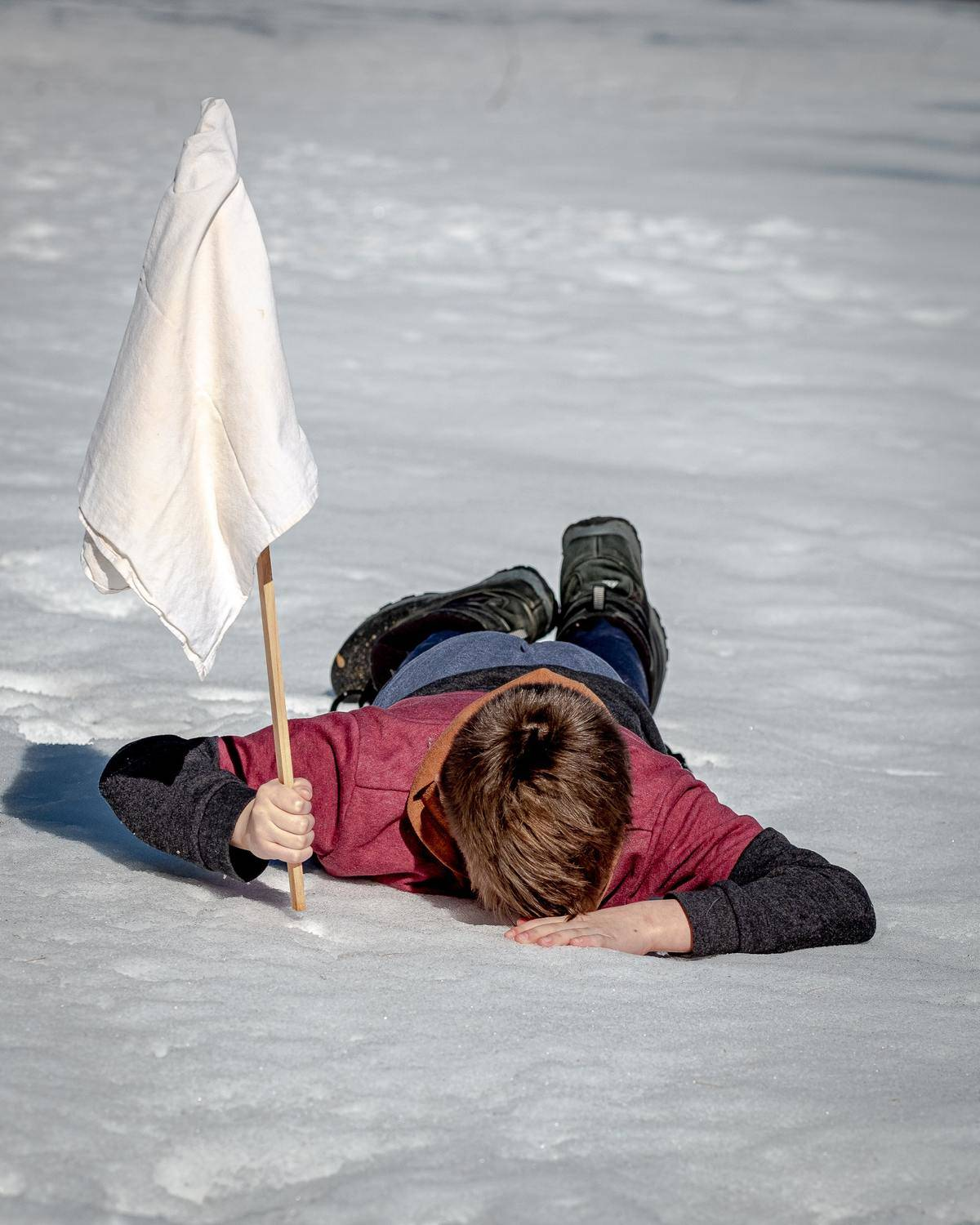 man laying on ice with white flag