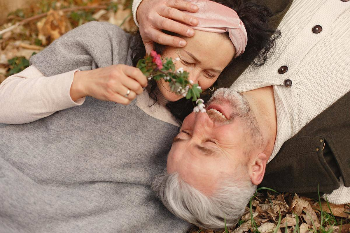 woman and man smiling while lying on the ground