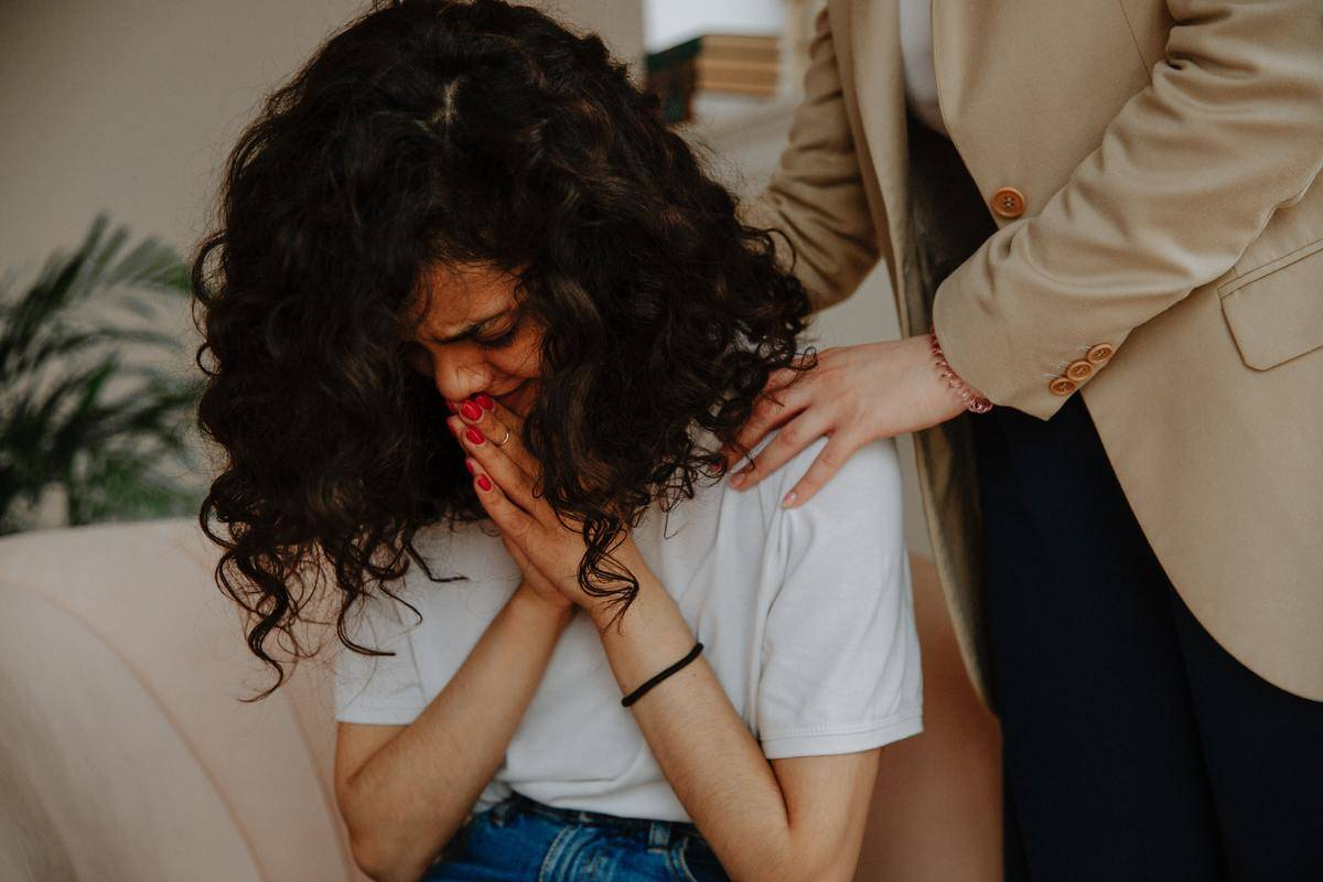 woman crying while being comforted
