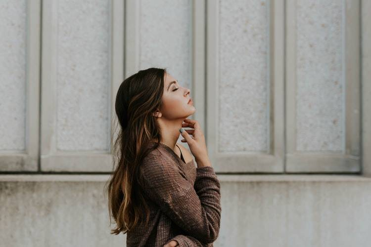side profile of woman staring up at the sky and thinking with her hand on her neck