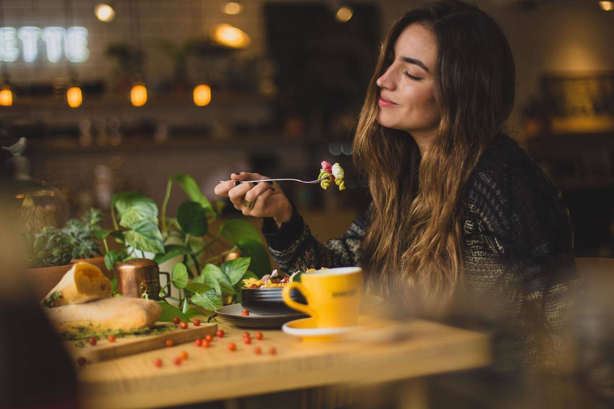 woman eating with fork and smiling