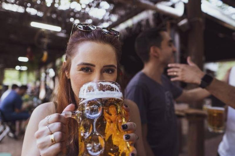 woman drinking large pitcher of beer staring at the camera