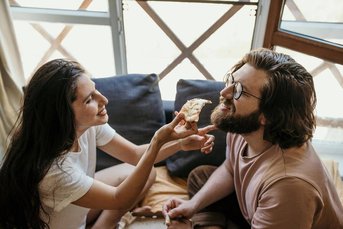 woman feeding pizza by hand to man in bed