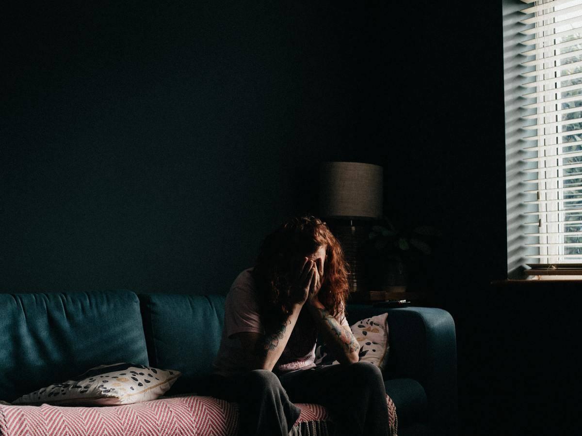 woman in shadows head in hands