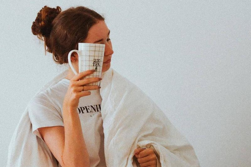 woman holding coffee mug to her face and wrapped in a blanket