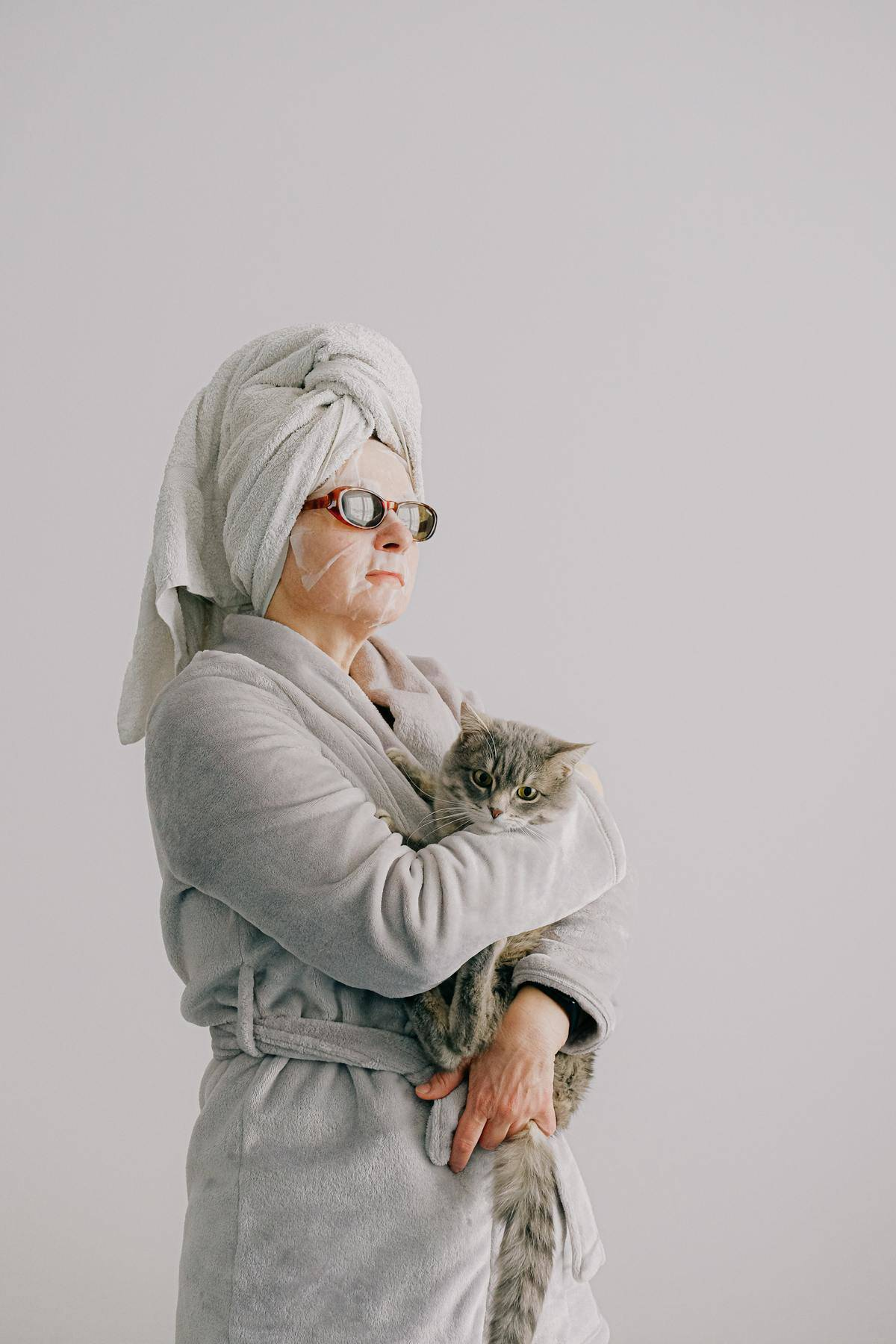 woman holing cat in towel and rob
