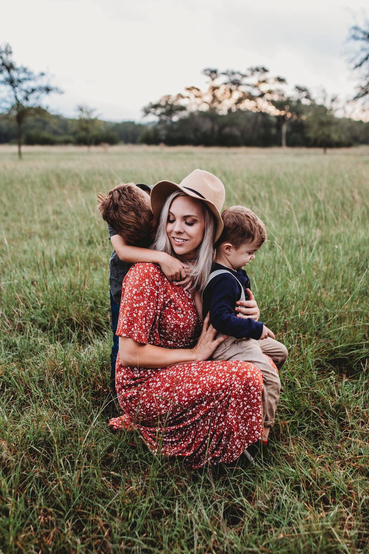 woman kneeling with her kids in a field