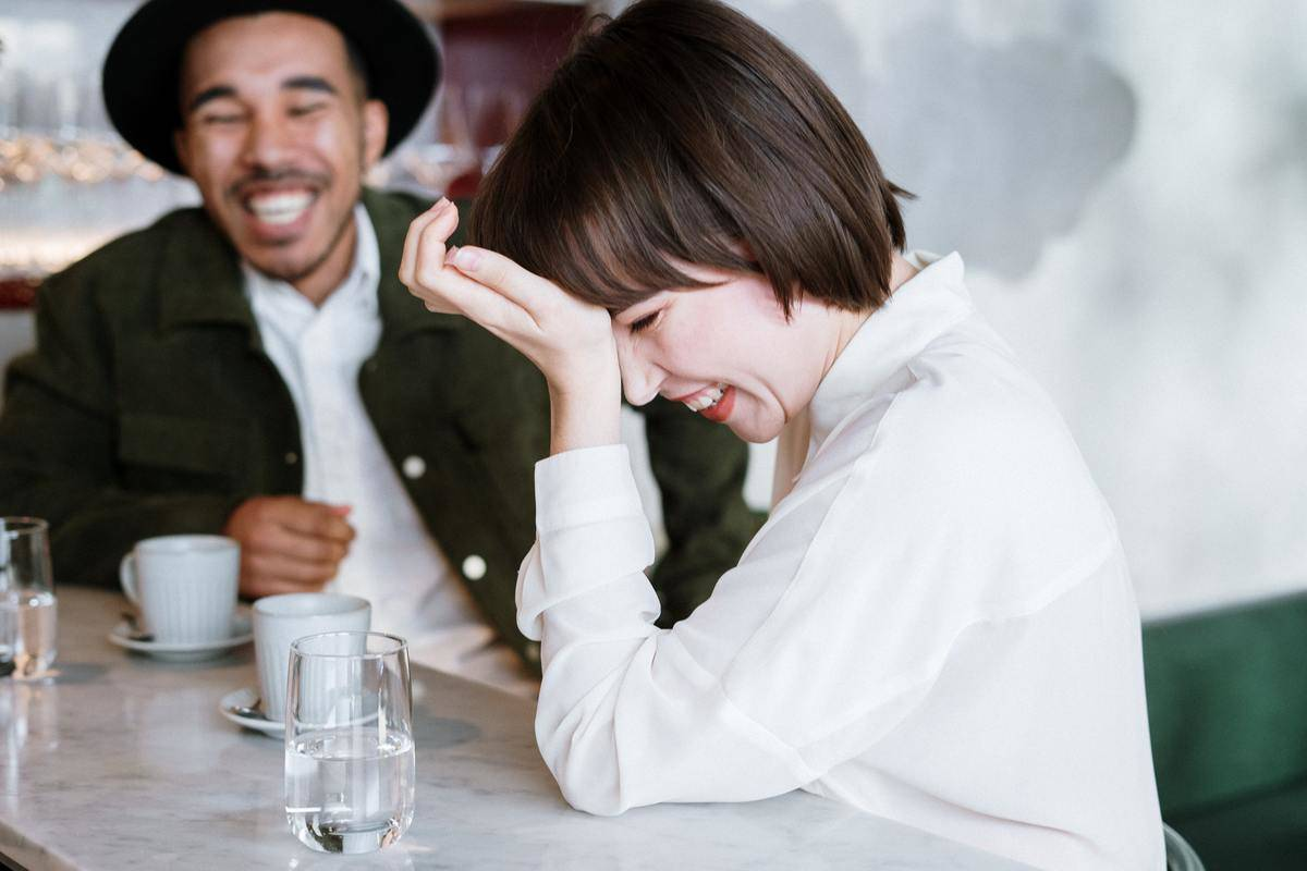 woman laughing with man at counter