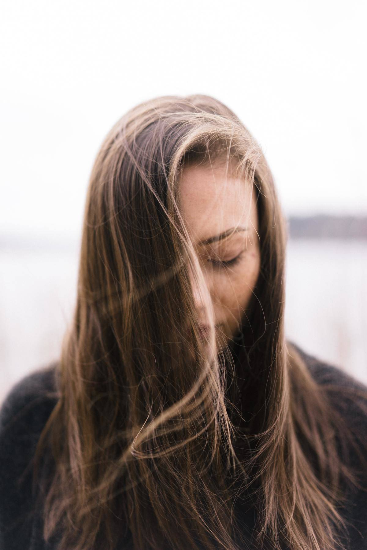 woman looking down with wind in hair