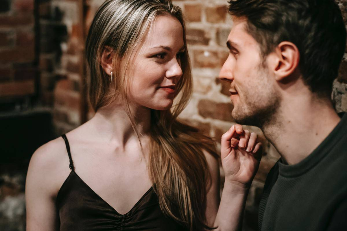 woman looks at man's face and smiles