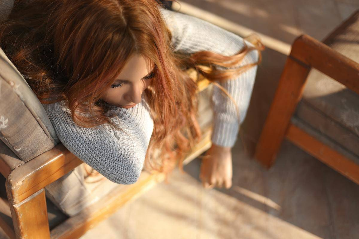 woman looks sad while leaning over chair