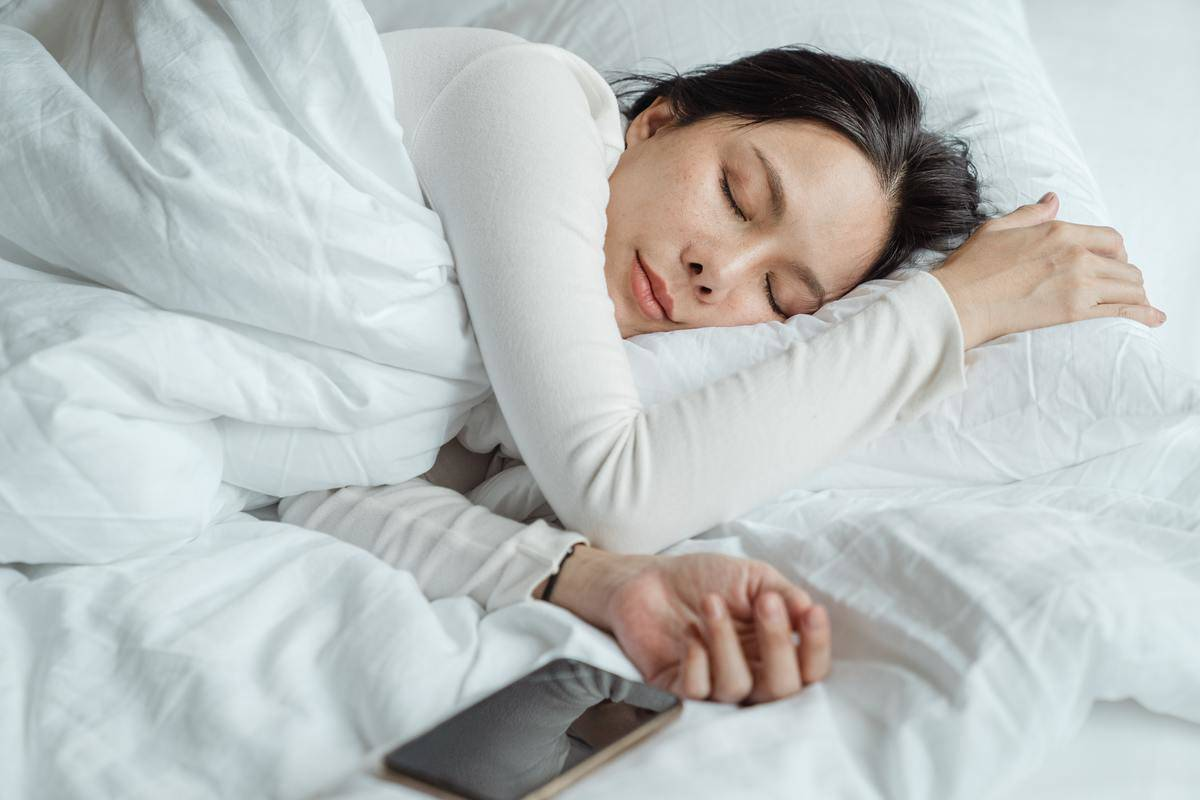 woman sleeping in bed with her phone