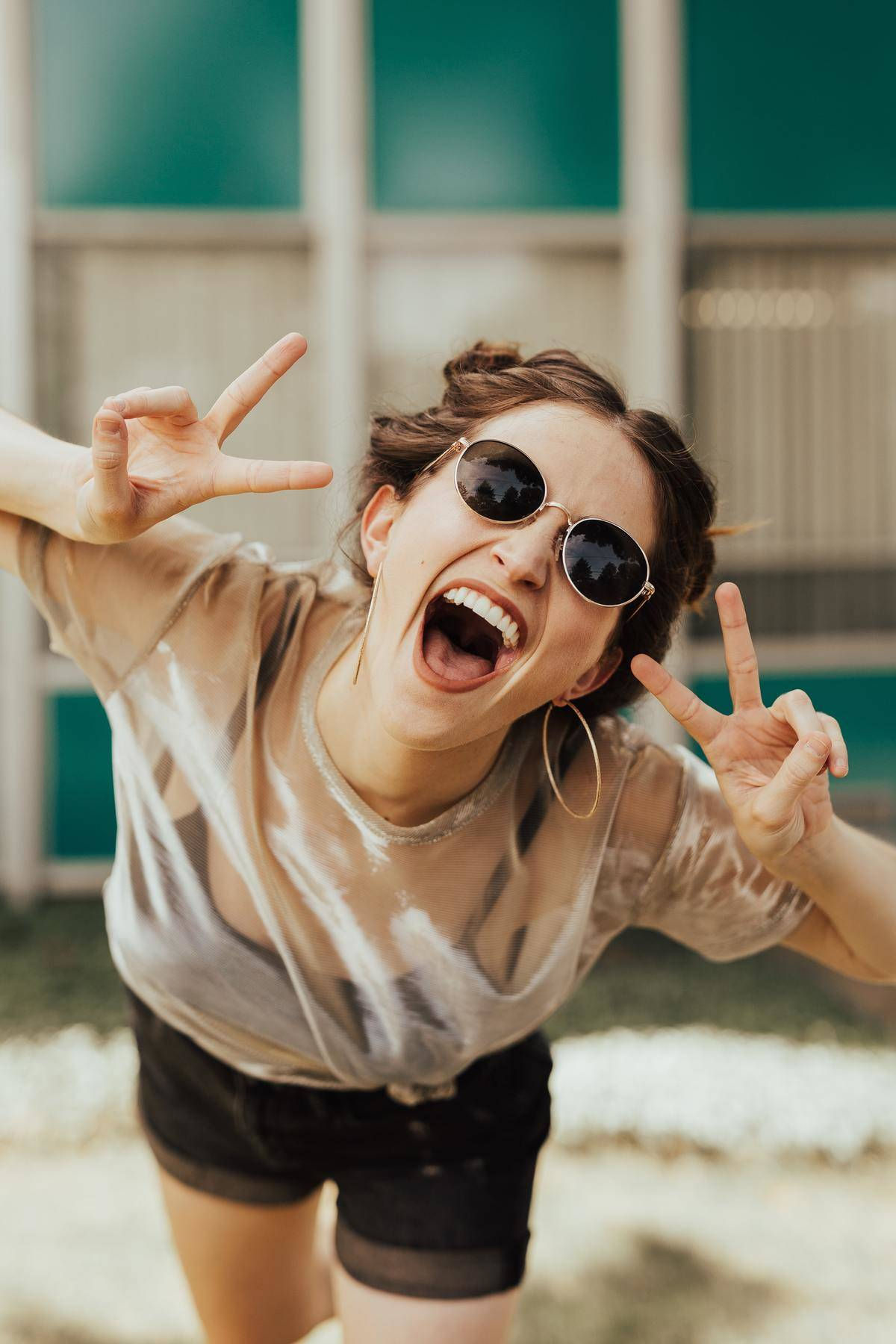 woman smiles with peace sign and glasses
