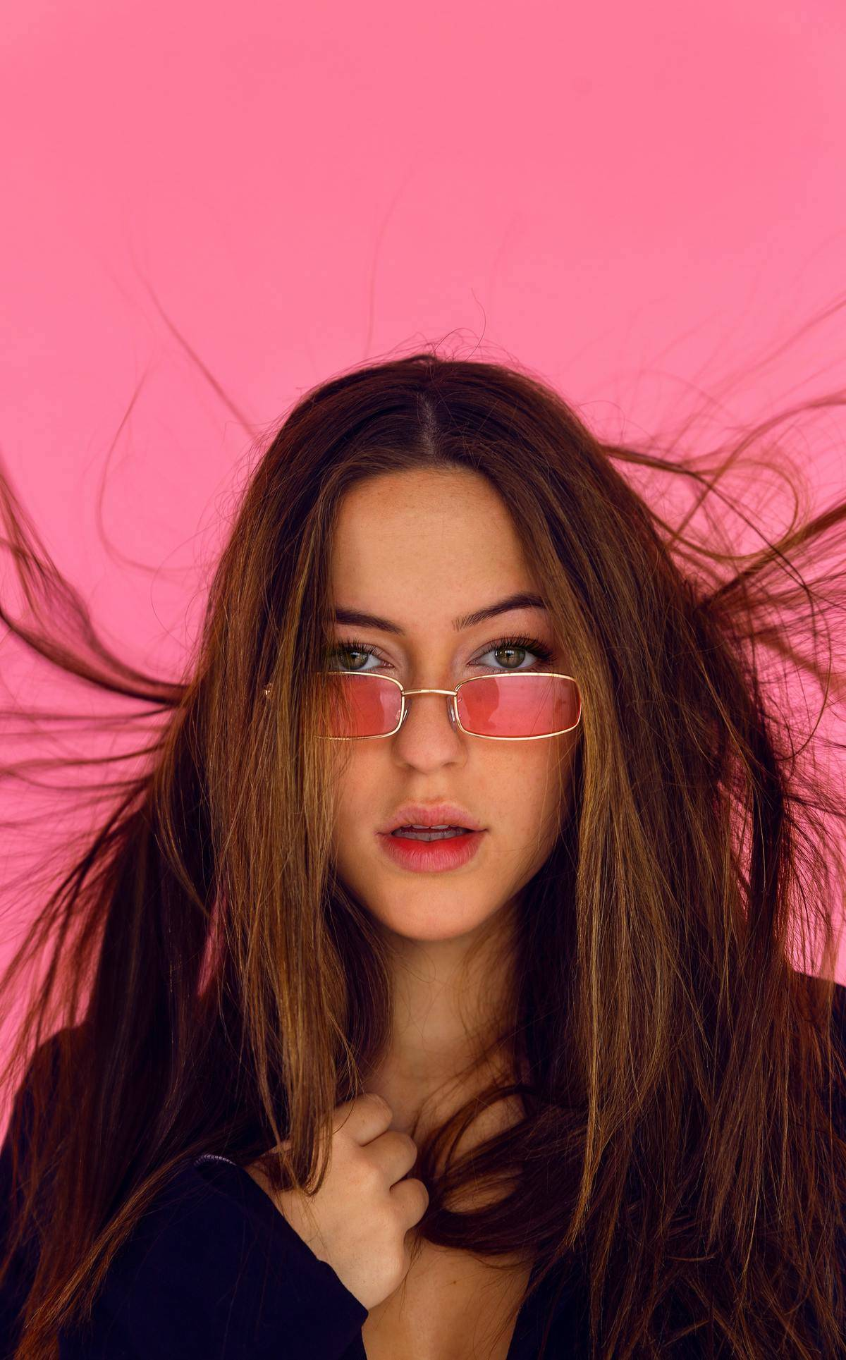 woman wearing pink shades with pink background