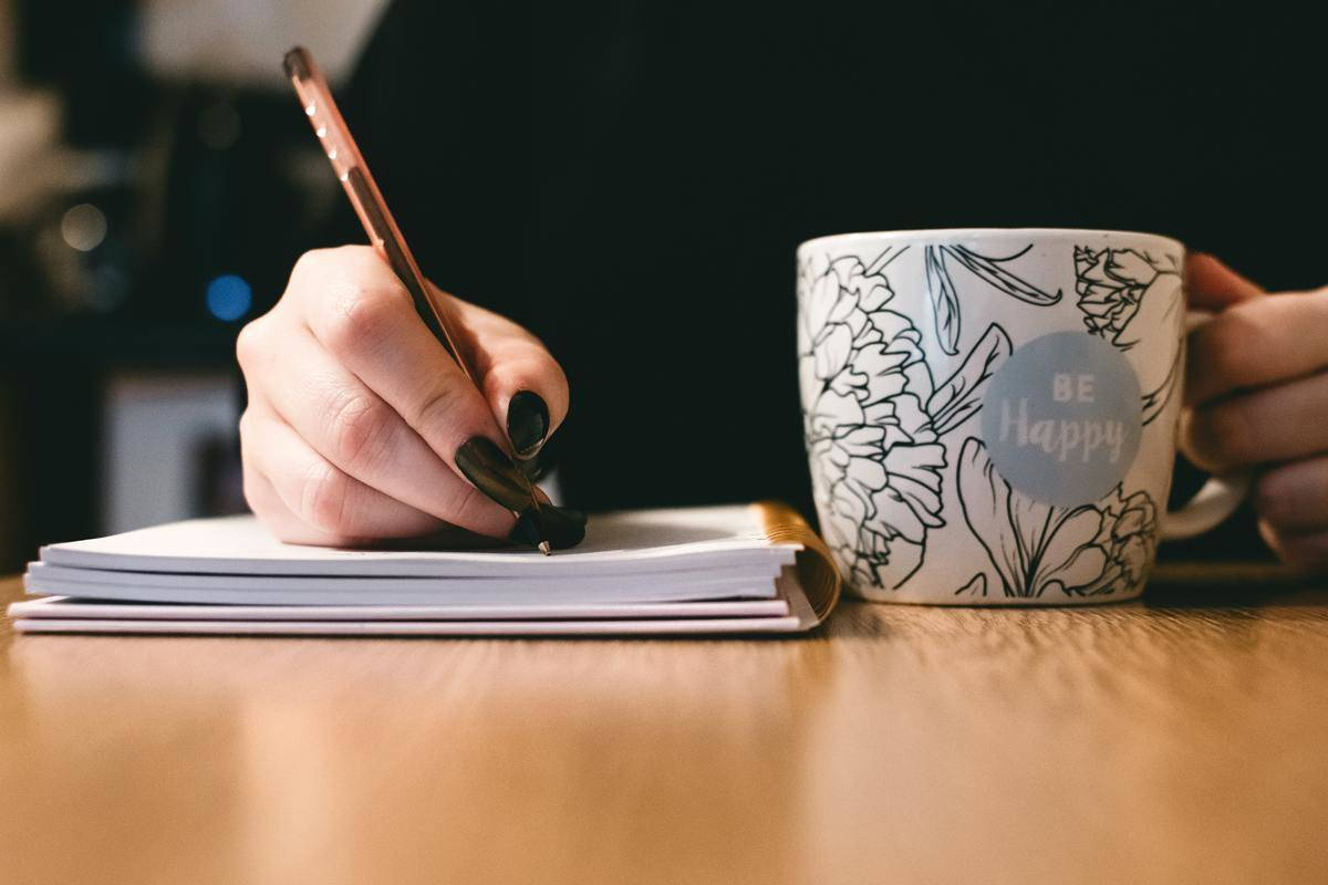 woman writing in journal beside mug