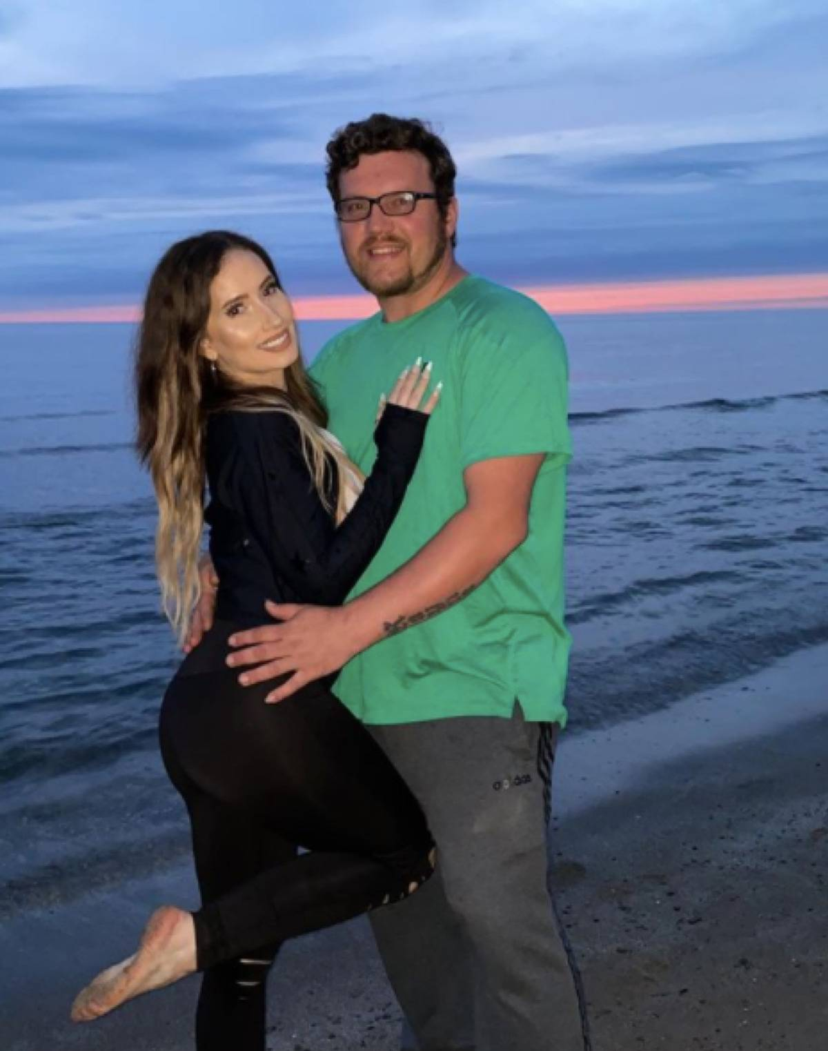 Alicia posing with her husband on the beach