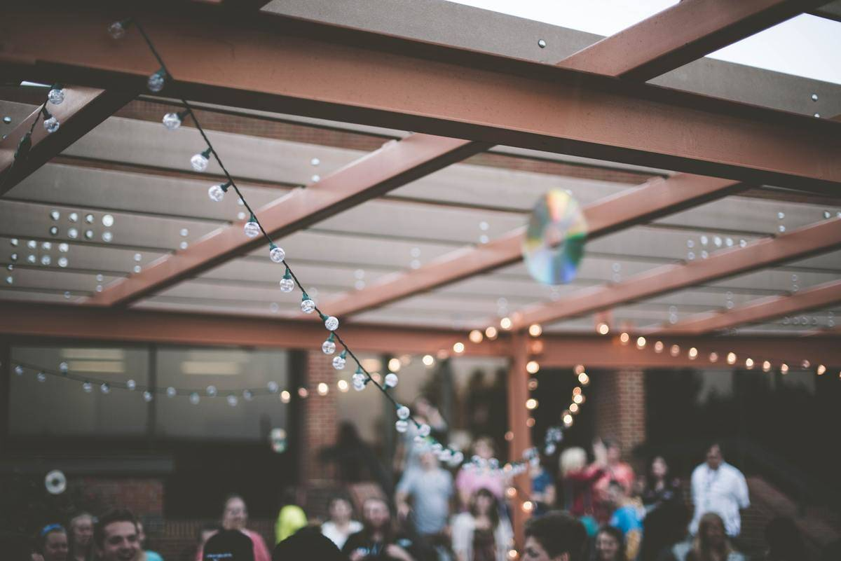 People gather on outdoor patio under string lights, at bar