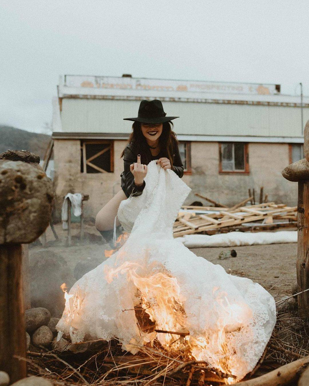 Woman gives middle finger while smiling and lighting wedding dress on fire