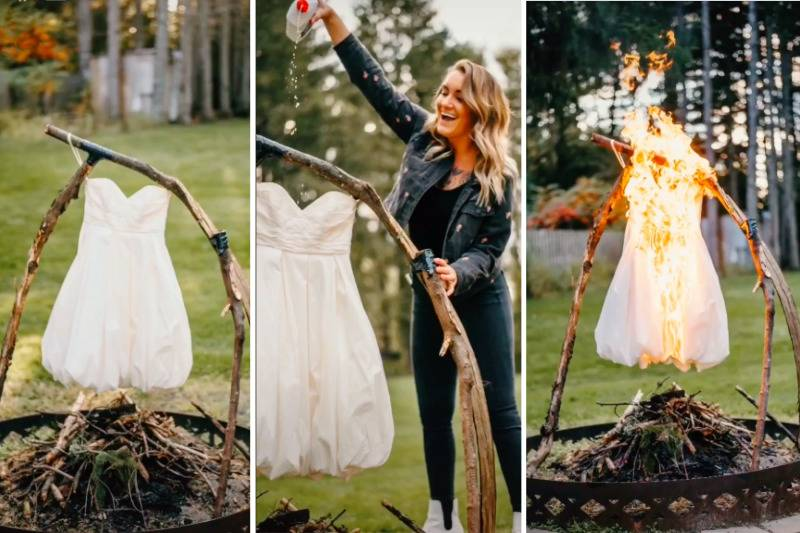 Woman smiles while pouring lighter fluid over a wedding dress hanging from log