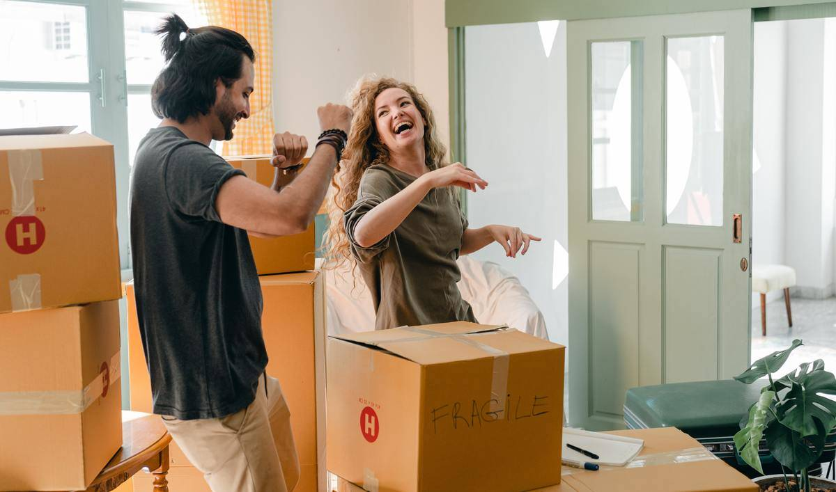 Couple laughs and dances while moving boxes around new home