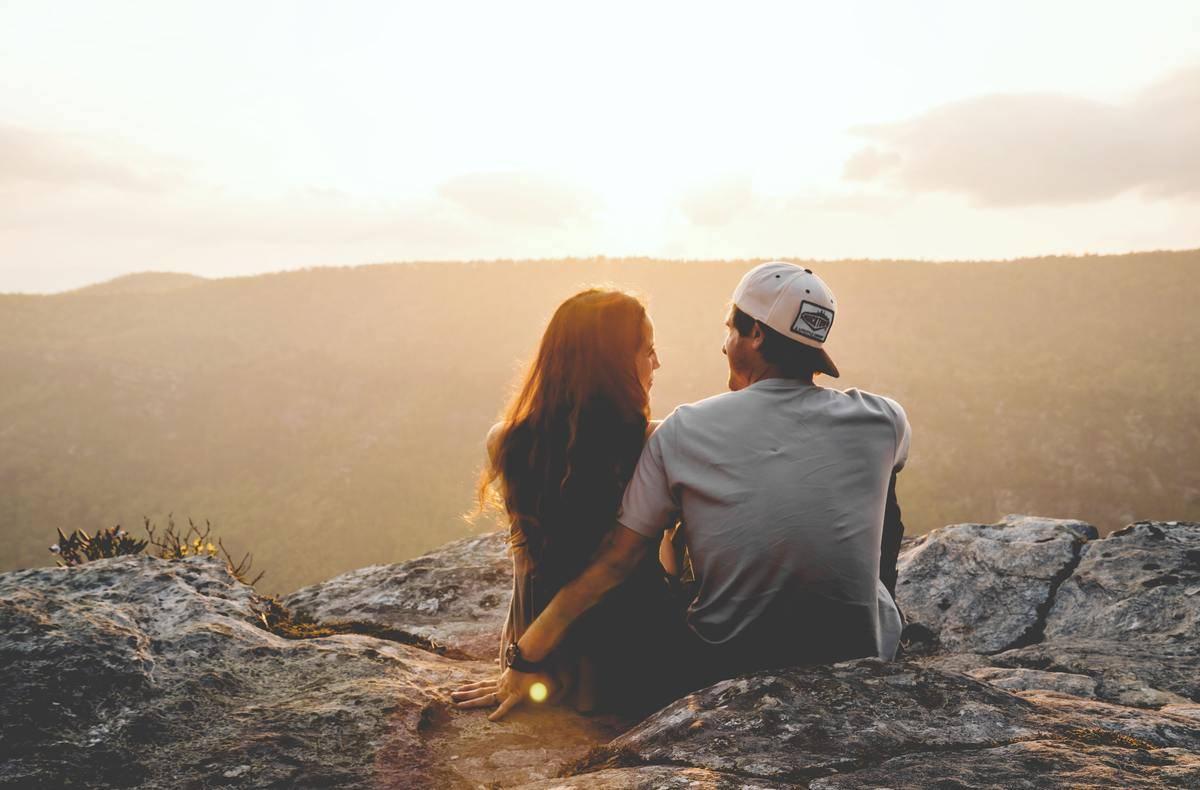Couple sit on ridge overlooking sunset