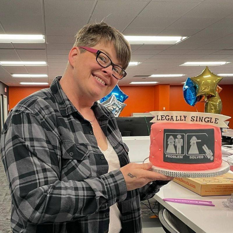 Woman smiles holding cake that says