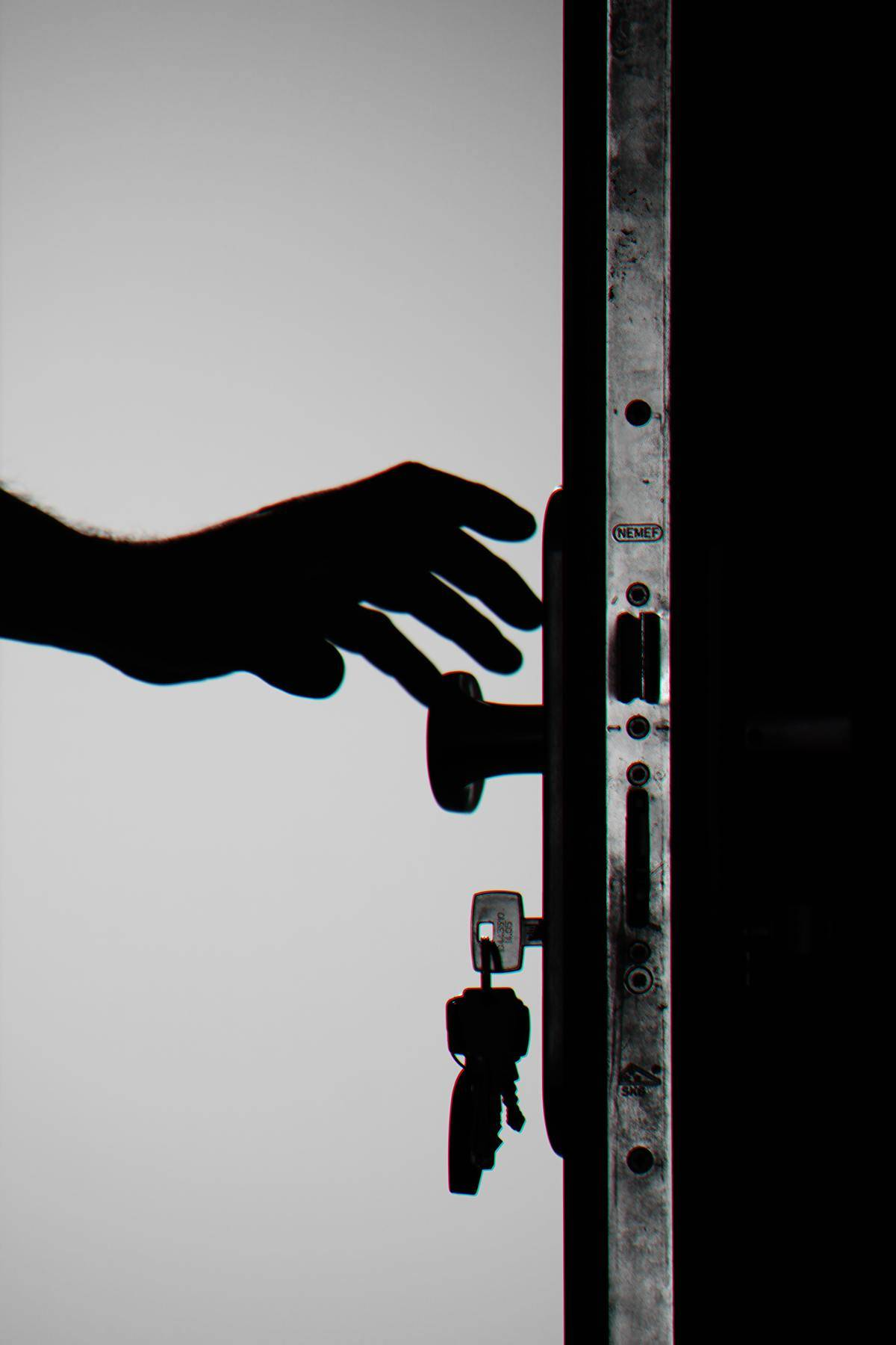 Hand reaching for doorknob with key