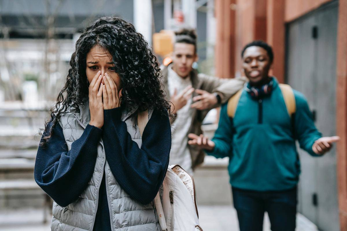 Woman stands clutching hands over mouth while men yell at her in distance