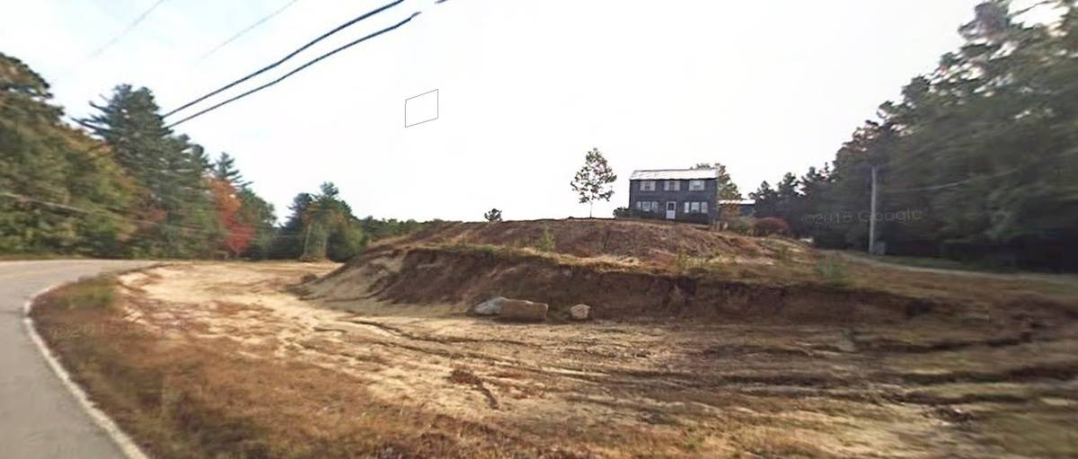 Large house is perched on a dirt mound hill with excavated ground surrounding it