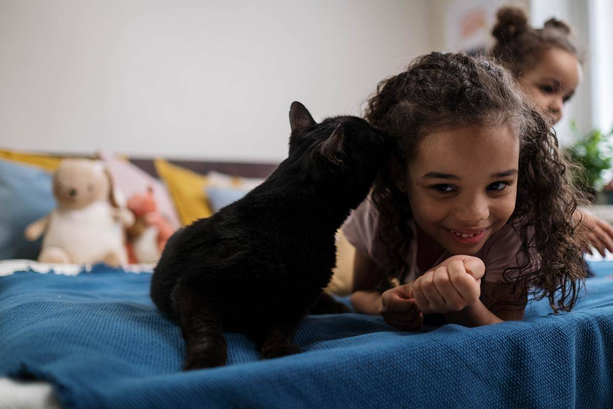Kids lie in bed with black cat smiling