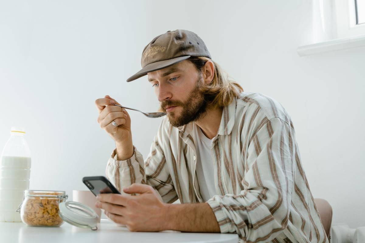 Man eats cereal while staring at his phone
