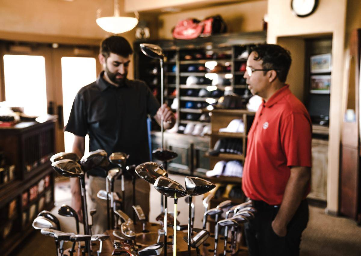 Two men in golf polo shirts in sporting goods store