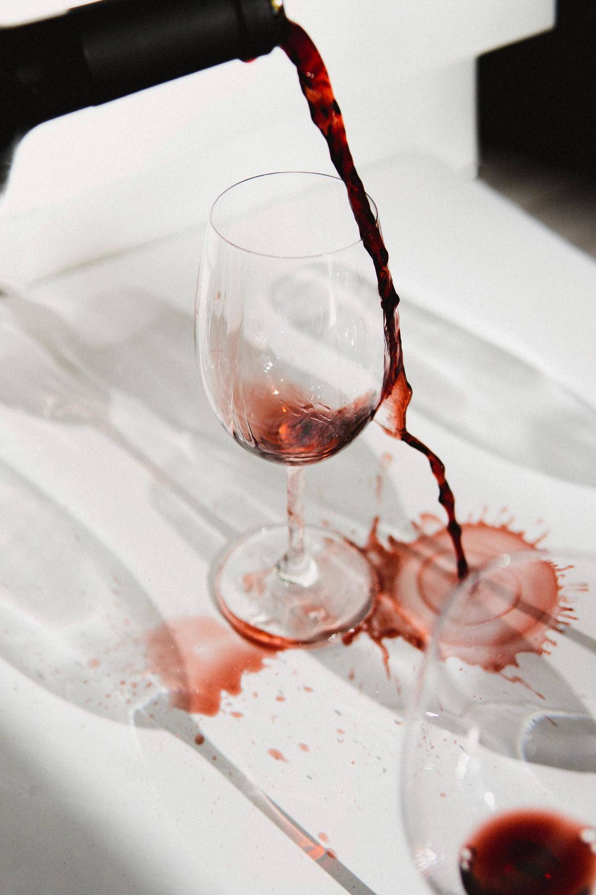 Red wine pouring over glass and hitting white table