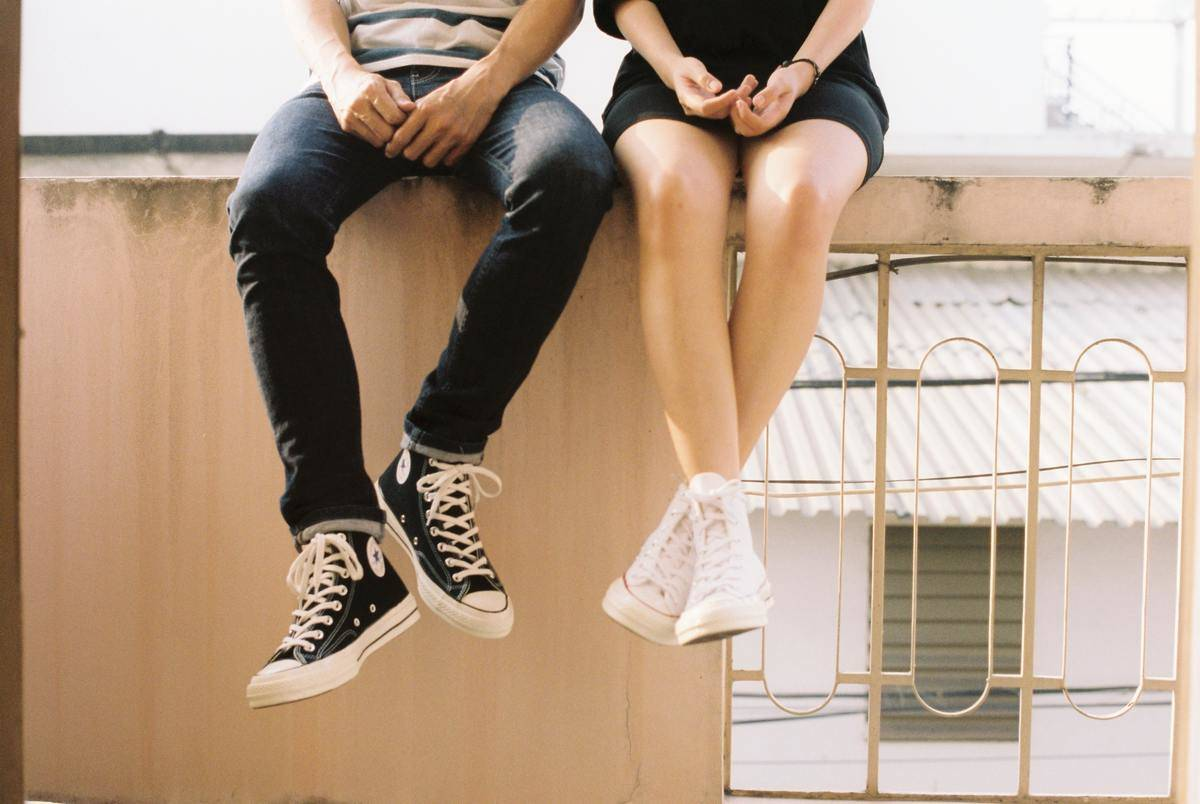 Two teens sit on cement wall, both wear converse with their feet dangling.