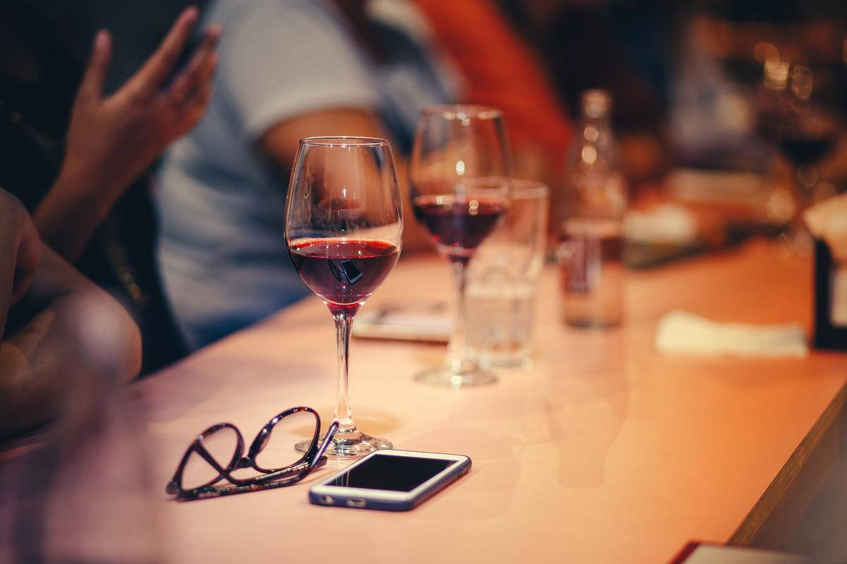 Half-empty glass of wine beside iPhone on table