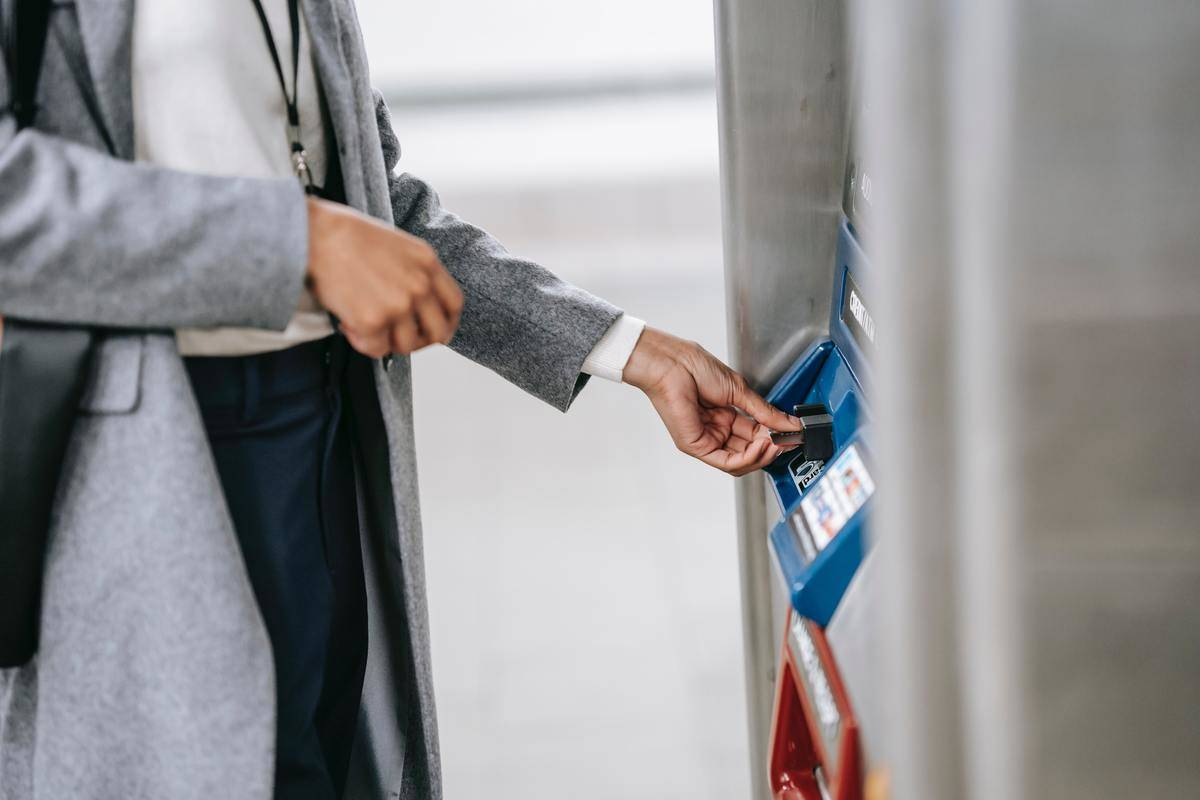 Woman stands at bank machine kiosk with card about to take money out of machine