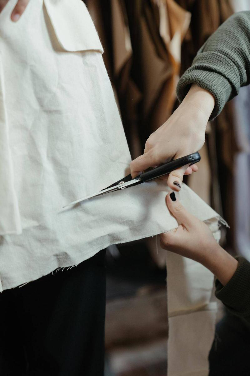 Woman's hands cutting white fabric with scissors