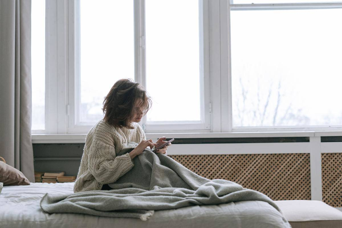Woman in large sweater with messy bed-head sits in bed scrolling on phone