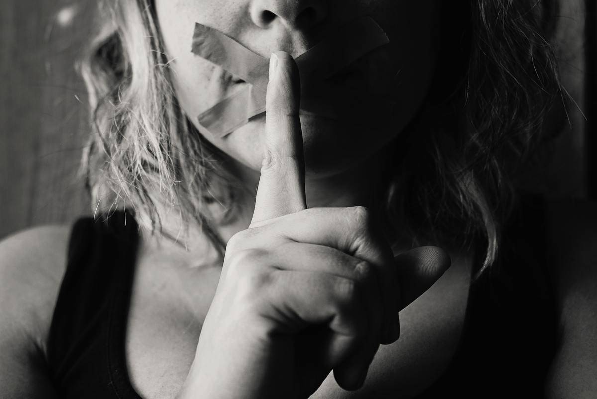 Woman with tape over mouth in X and finger