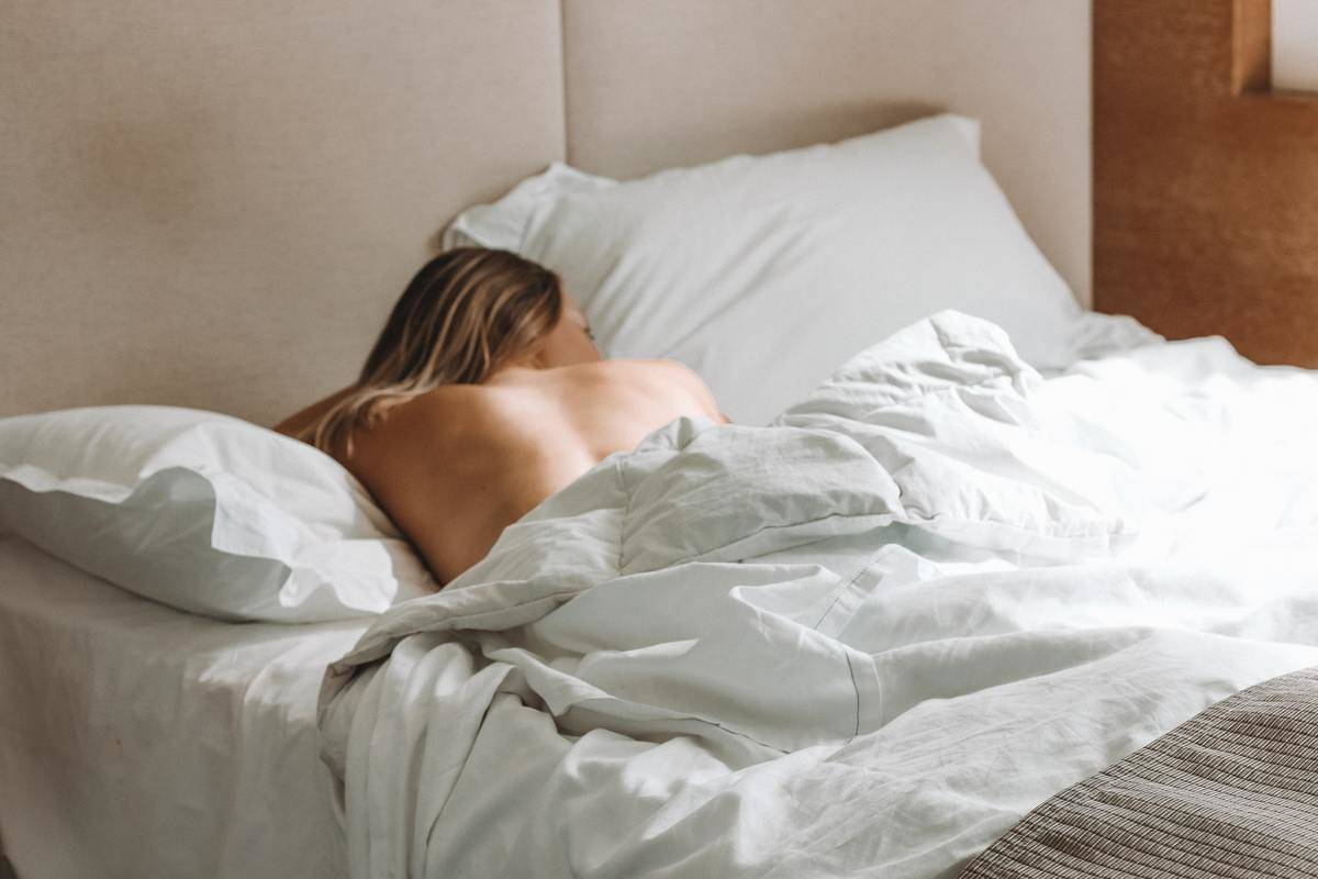 Woman lays in bed with back exposed