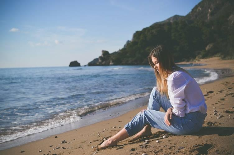 woman sitting down looking sad at the beach
