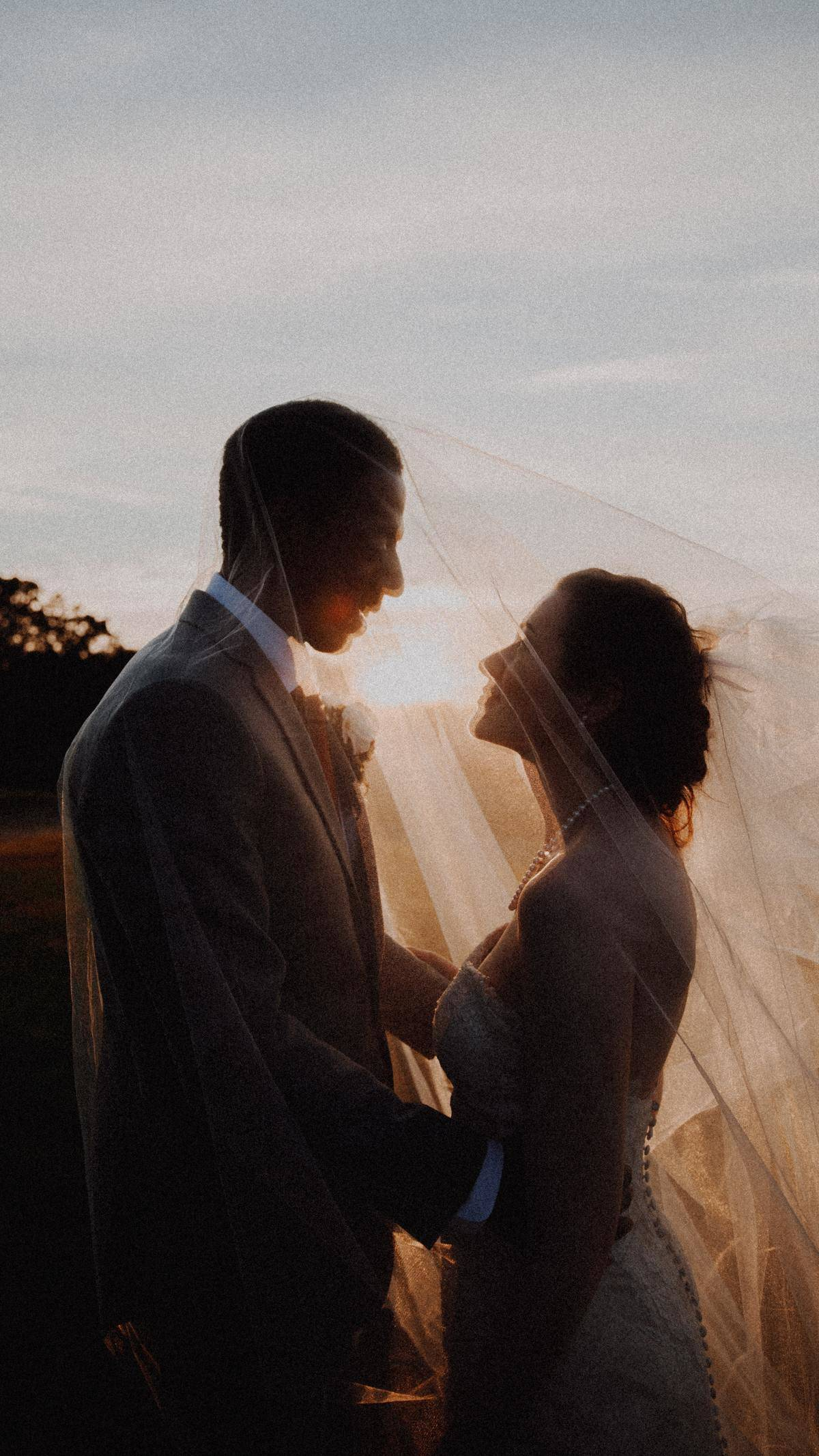 bride and groom in sunset looking at each other