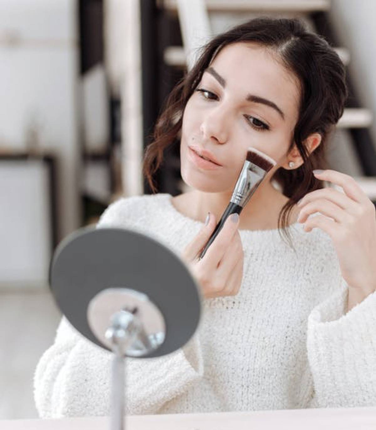 woman putting makeup on in the mirror