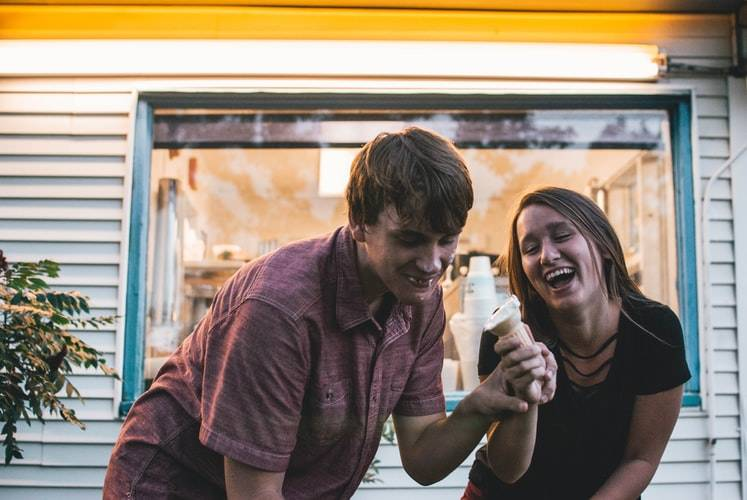 couple laughing and sharing an ice cream cone