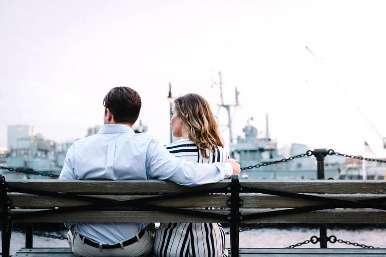 back shot of couple sitting on park bench, the woman is looking at the man but he is looking away