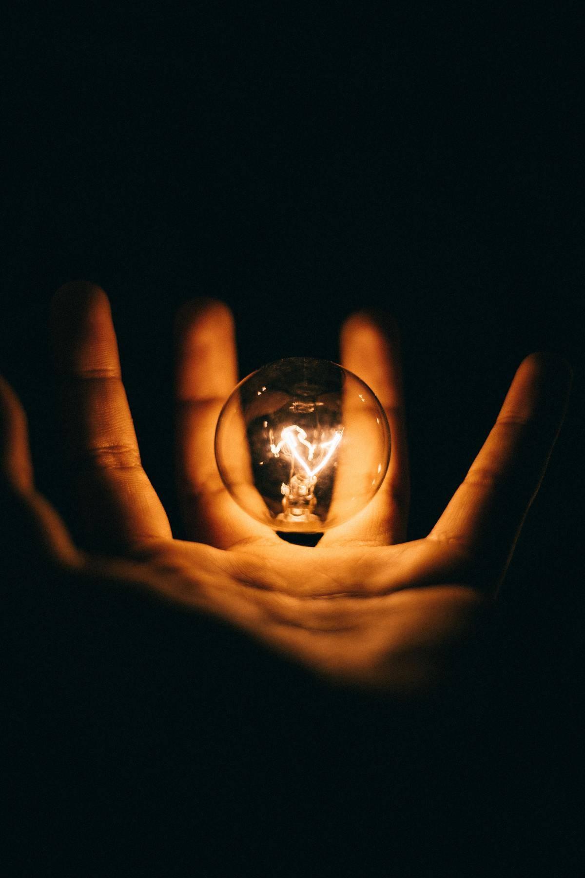hand holding lightbulb that's lit