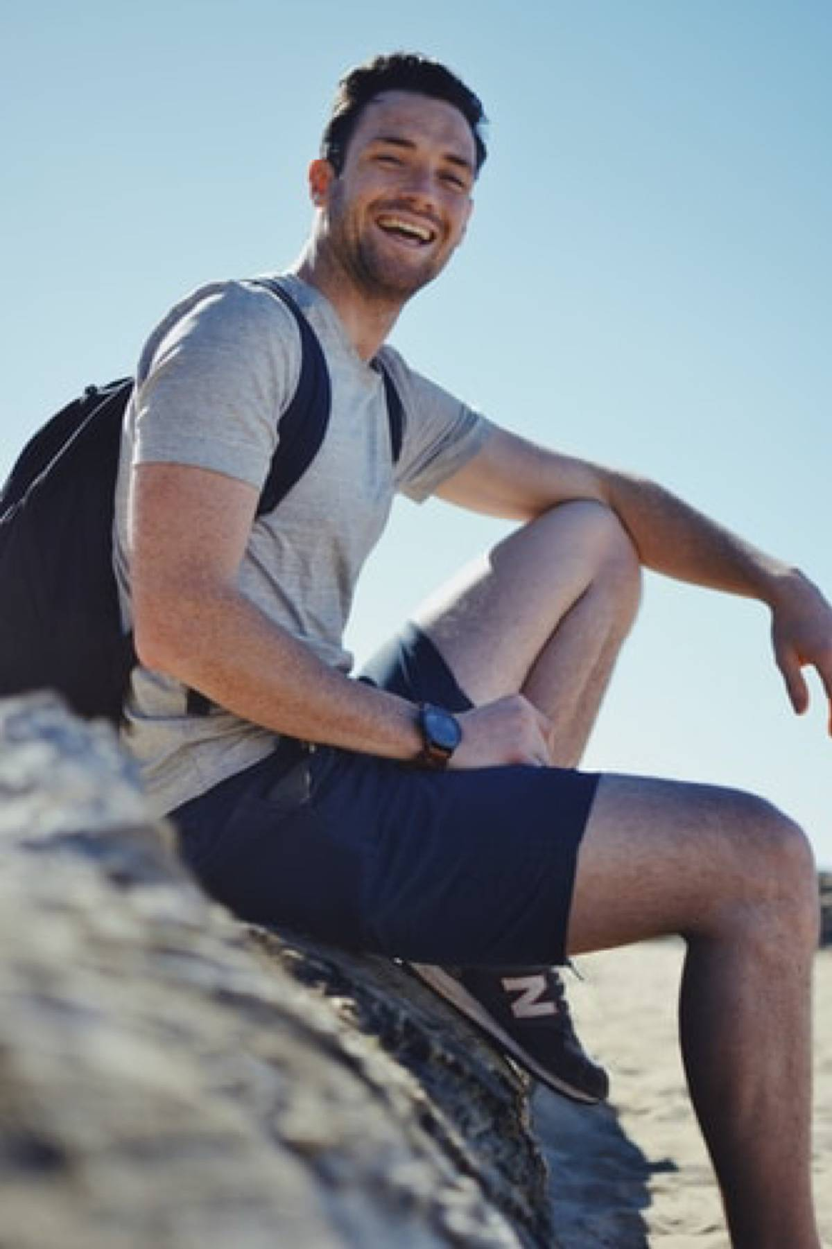 man laughing and smiling sitting on a rock