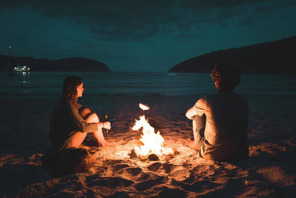 man and woman sit at bonfire on the beach
