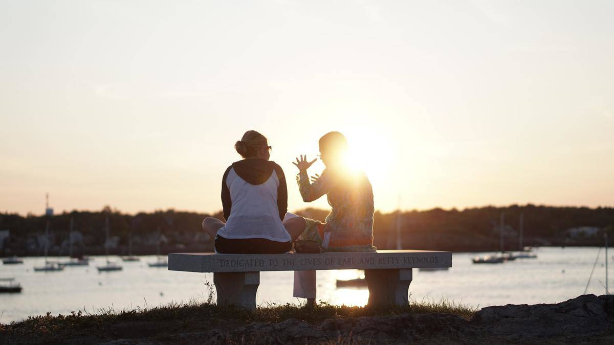man and woman sit on bench by the sun