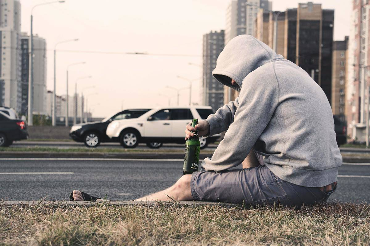 man having a beer on the ground on the street
